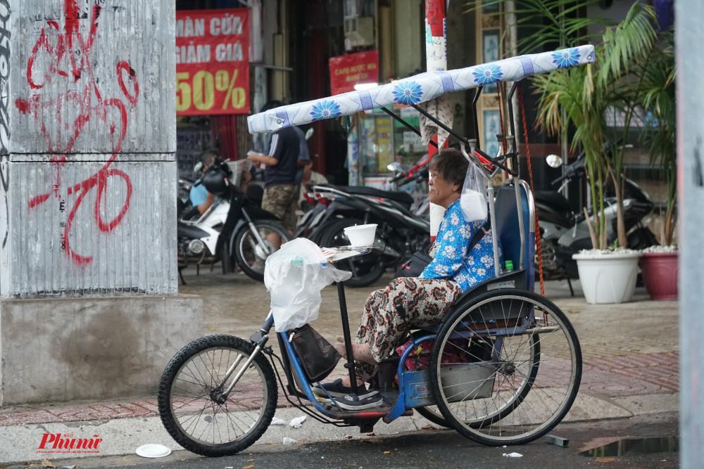 Cô bán vé số ngồi nhìn mưa khi những tờ vé số đã được che chắn cẩn thận