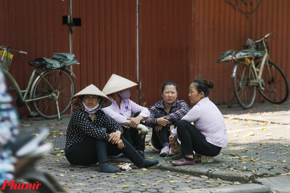 Phút nghỉ ngơi trong bóng mát trước cổng công trường của những người lao động.