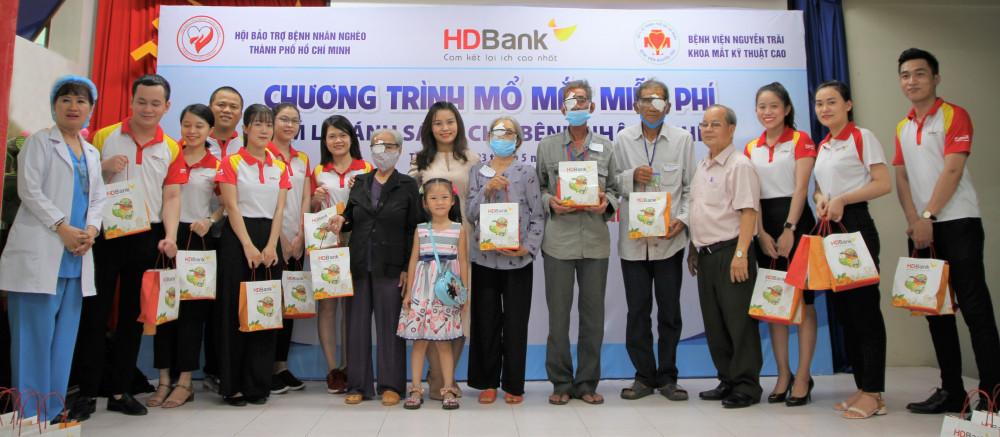 Bà Trần Thu Hương - Phó giám đốc phụ trách Khối vận hành HDBank (áo trắng đứng giữa) và cán bộ, nhân viên HDBank trao quà cho bà con. Ảnh: HDBank cung cấp