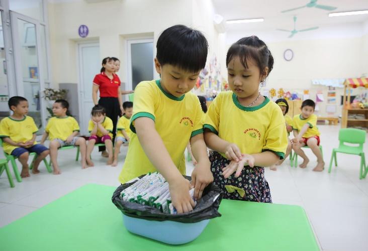 Các em học sinh được hướng dẫn cách gấp gọn và thu dọn hộp sữa sau khi sử dụng xong. Ảnh: Vinamilk cung cấp