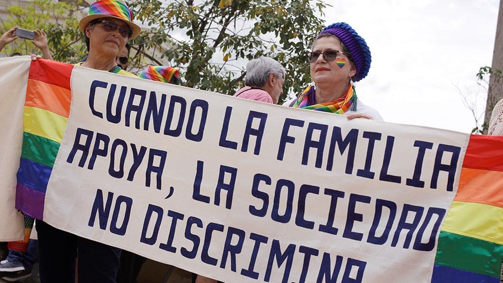 Các thành viên cộng đồng LGBT và các nhà hoạt động với tấm biểu ngữ ghi khi gia đình ủng hộ, xã hội sẽ không phân biệt đối xử.