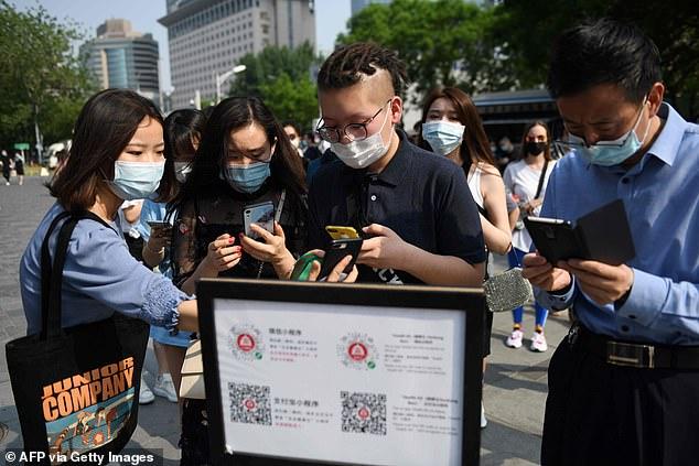 Người dân Hàng Châu quét mã bằng điện thoại để chứng minh sức khỏe trước khi vào trung tâm mua sắm.