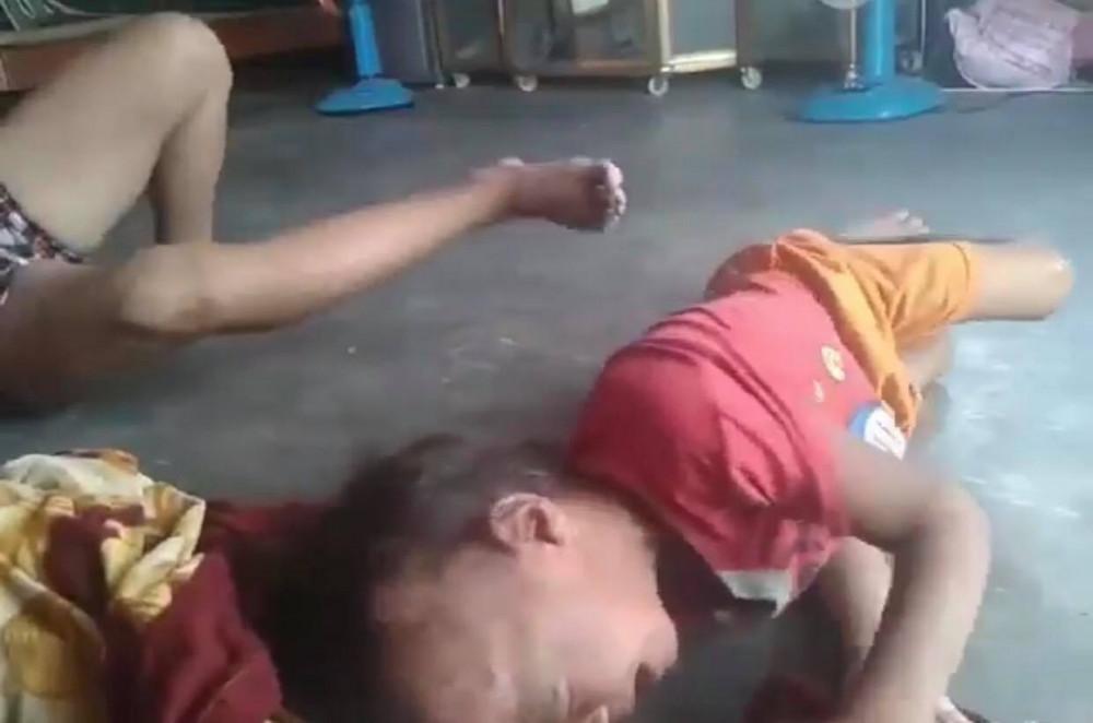 Mặc dù nằm xuống nhưng người này vẫn dùng chân đạp vào người bé trai