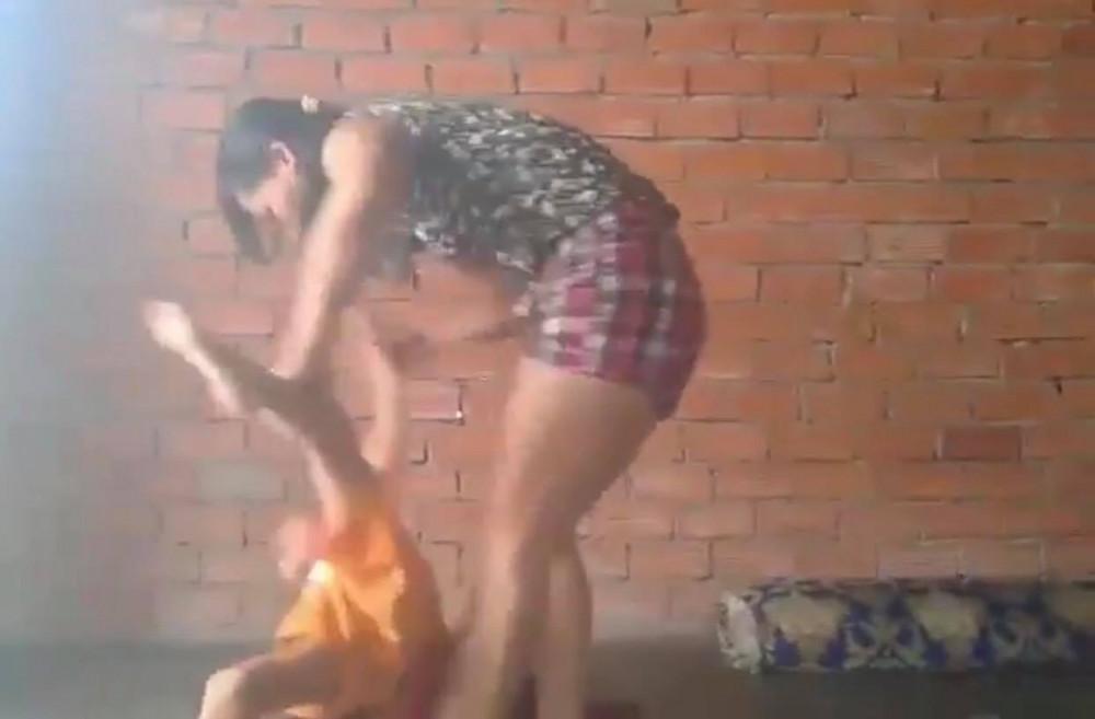 Người phụ nữ nhấc cả người bé trai lên đánh đập