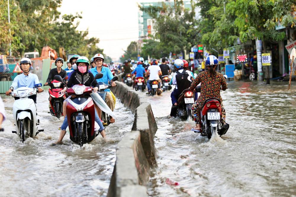 Chỉ sau một cơn mưa lớn, không ít tuyến đường ở thành phố biến thành những dòng sông đen - ảnh: Minh Thanh
