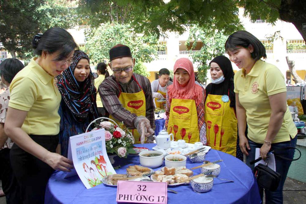 Bà Trần Thị Phương Hoa (bìa phải) - Phó chủ tịch Hội LHPN TP.HCM thăm góc bếp thi của giađình anh Ro Kak,  dân tộc Chăm, P.17, Q.Bình Thạnh