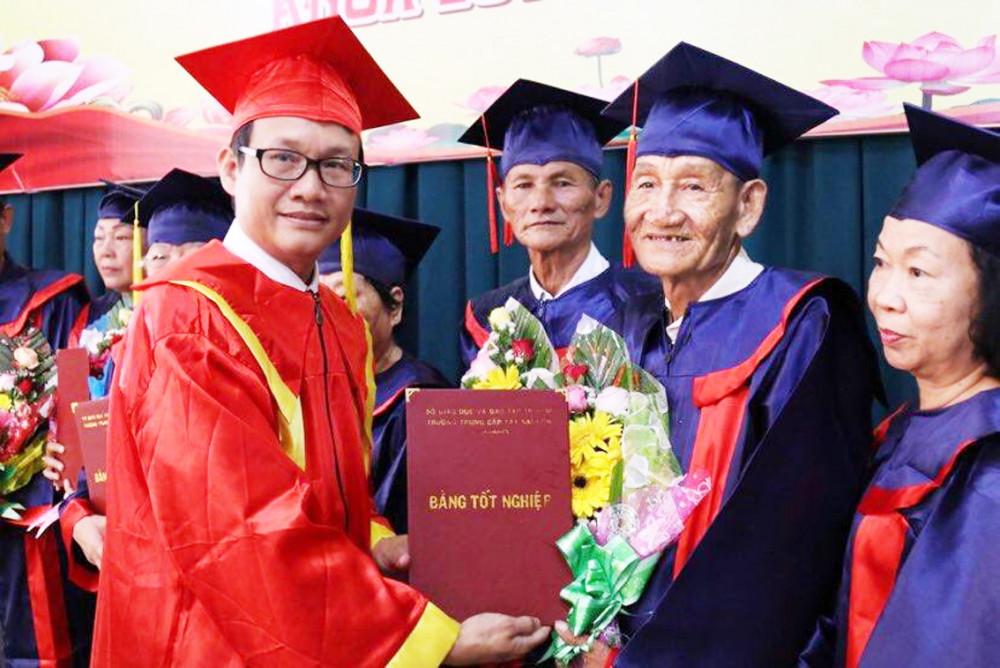 Ông Nguyễn Khắc Thương, Hiệu trưởng nhà trường, trao bằng cho cụ Bùi Văn Mưa