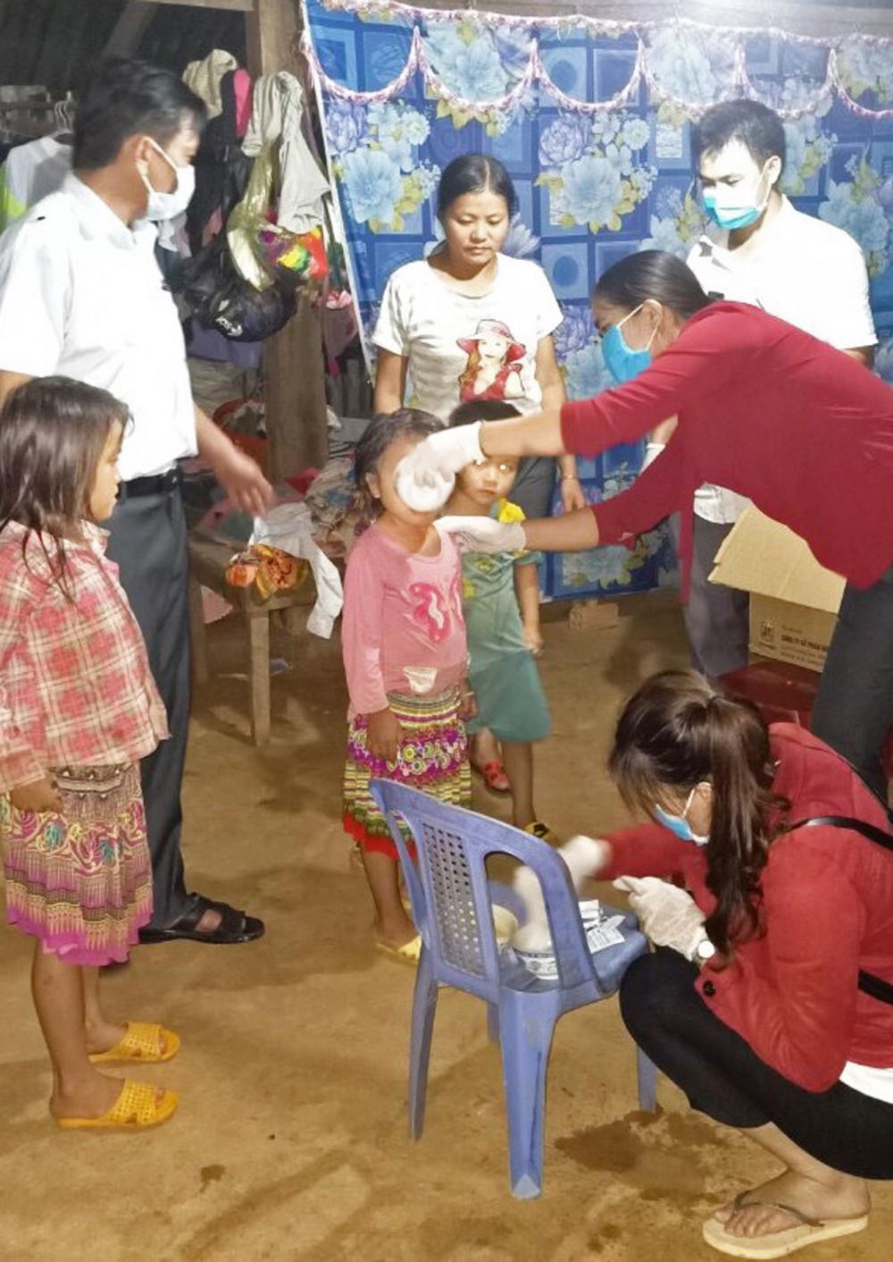 Cán bộ y tế cho người dân khu vực có dịch uống thuốc, tiêm phòng