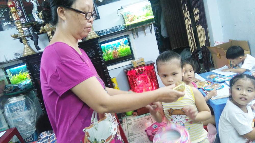 Cô giáo Trần Thị Hạnh rèn chữ cho học trò trong xóm nhỏ - Ảnh: HẠNH CHI