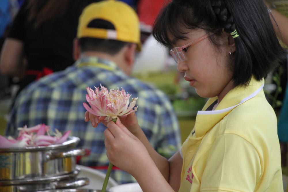 Dù tuổi còn nhỏ, nhưng suốt quá trình dự thi, cô bé là một bếp phụ rất chu đáo tỉ mỉ, Hết cắt gọt trái cây, lại tỉa hoa sen trang trí mâm cơm.