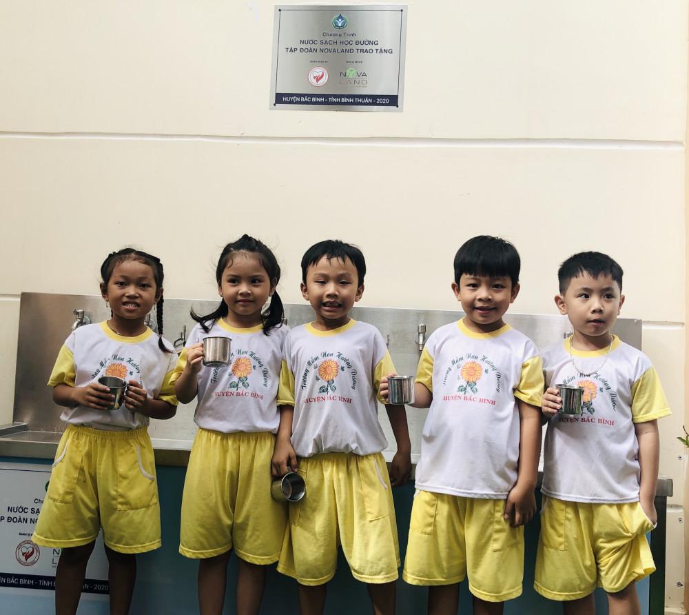Các em học sinh bên hệ thống máy lọc nước uống sạch. Ảnh: Novaland cung cấp