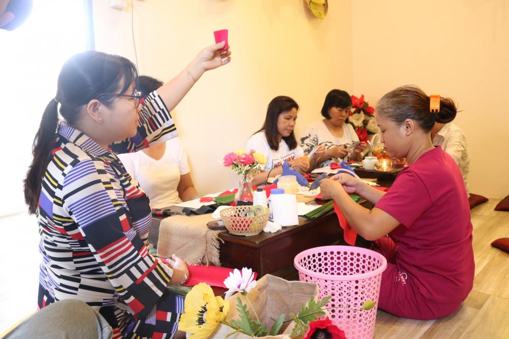 Chị Trần Thị Minh Nguyệt (bìa trái) - Phó chủ tịch Hội LHPN quận Thủ Đức - hướng dẫn các dì, các chị sử những thao tác đầu tiên với giấy, keo để làm hoa.