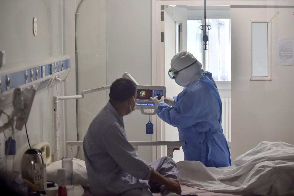 Nhân viên y tế kiểm tra bệnh nhân COVID-19 tại bệnh viện ở Bắc Kinh