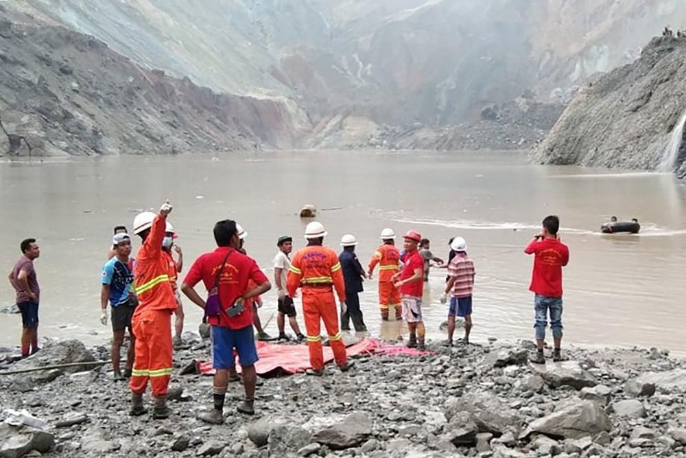 Các cứu hộ viên phối hợp cùng người dân tìm kiếm nạn nhân còn mắc kẹt trong bùn.