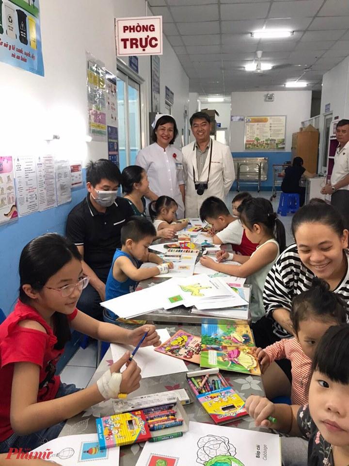 Bác sĩ Nguyễn Anh Tuấn - Trưởng khoa Nội Tổng quát 2 cùng điều dưỡng Nguyễn Thị Rảnh tổ chức chức các em tô màu tại khoa
