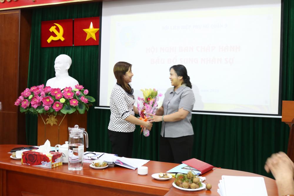 Bà Nguyễn Thị Ngọc Linh (bìa trái) - Trưởng ban Tổ chức - Kiểm tra, Hội LHPN TP.HCM - tặng hoa chúc mừng bà Nguyễn Hạnh Thảo nhận nhiệm vụ mới.