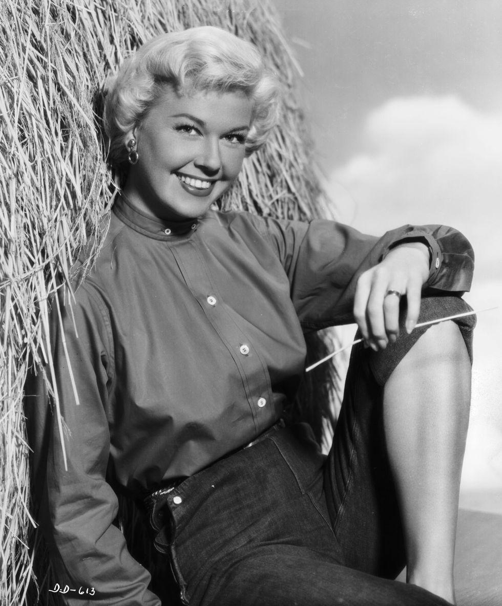 Doris Day khoe cơ thể cân đối với trang phục hàng ngày trong một tấm ảnh chân dung chụp tại Warner Brothers Studio năm 1951. Cô kết hợp quần jean với chiếc áo cổ cao cài kín nút.