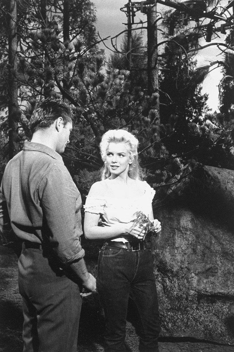 Marilyn Monroe kết hợp một chiếc quần jean wash sẫm màu lưng cao, thắt lưng khóa rộng và áo trắng cổ rộng, chất liệu mềm mại trong một cảnh quay với  Robert Mitchum.