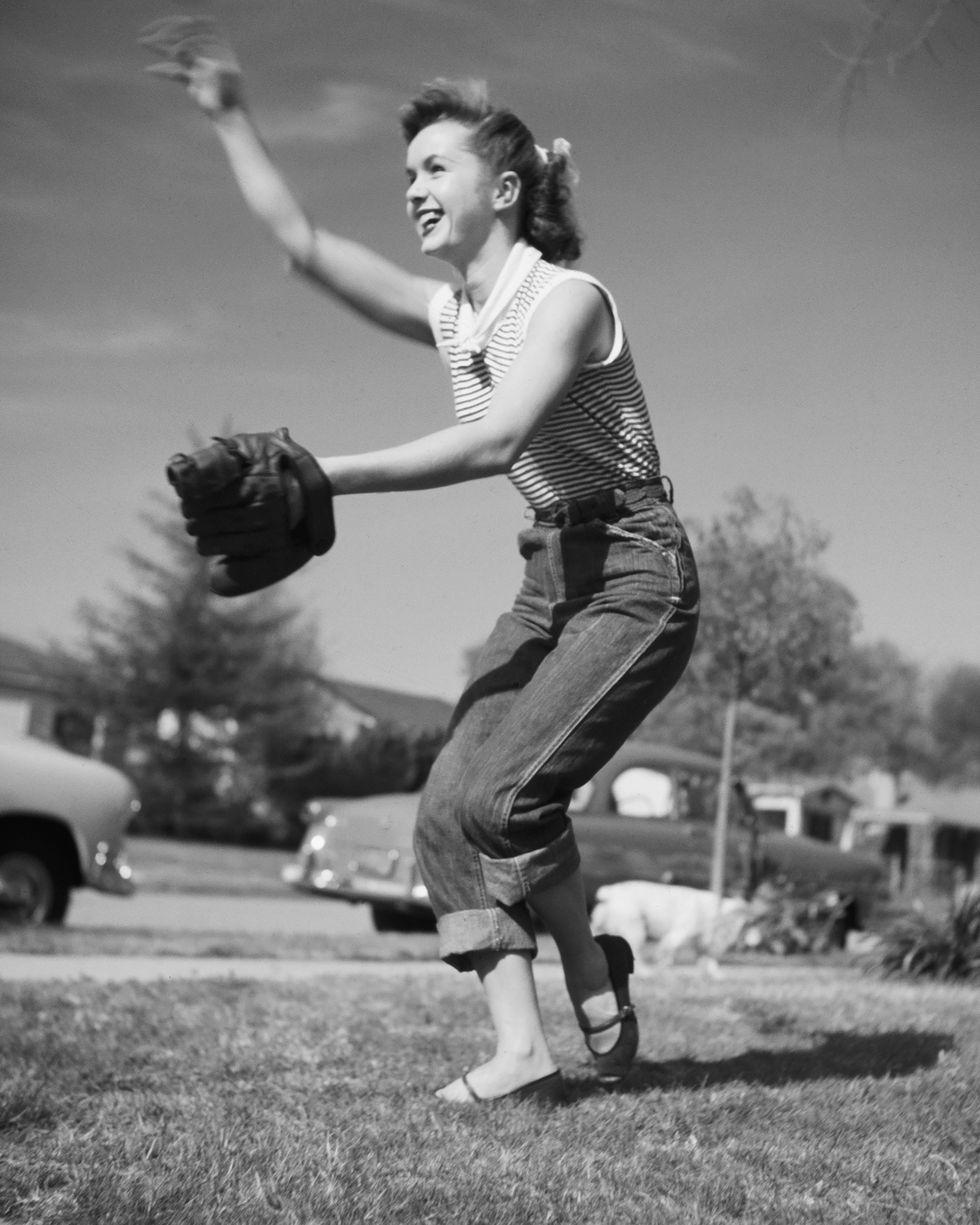 Debbie Reynolds đã phối quần jean xắn lai cao với chiếc áo tan top cùng phụ kiện đi kèm là chiếc nơ cột tóc khi tham gia trận đấu bóng chày năm 1950.