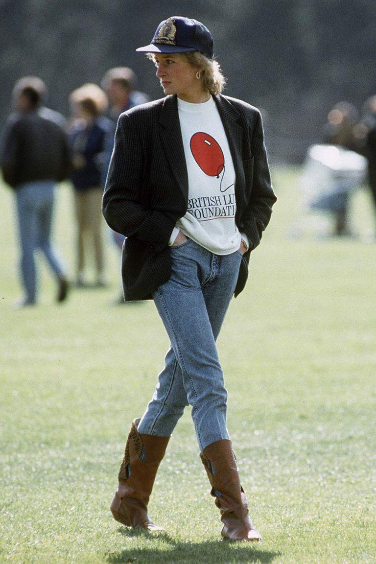 Ảnh chụp khi công nương Diana đi dạo trên bãi cỏ câu lạc bộ Guards Polo với chiếc quần jean lưng cao, phần ống nhét trong đôi bốt cổ cao, áo thun cổ tròn và áo khoác blazer bên ngoài.