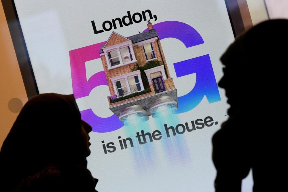 Quảng cáo mạng dữ liệu 5G tại một cửa hàng điện thoại di động ở London (Anh) - Ảnh: Reuters