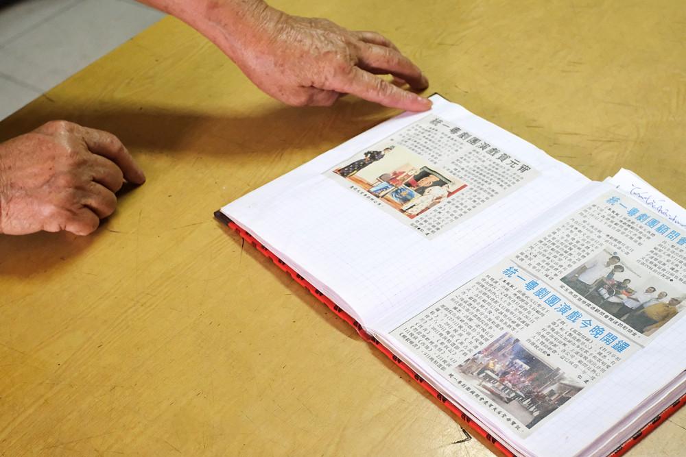Bà Hà mở lại những trang báo gắn liền với những tiết mục của Đoàn Ca kịch Thống Nhất Quảng Đông- Ảnh: Thanh Hoa