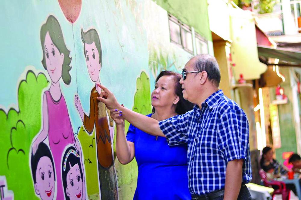 Vợ chồng chị Thu - anh Hồng bên bức tường trong hẻm 27 Trần Tuấn Khải, nơi ghi dấu nét vẽ của chị với thông điệp mọi người hãy chung tay bảo vệ môi trường