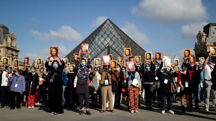 Hướng dẫn viên du lịch Paris cầm áp phích mô tả bức tranh Mona Lisa của nghệ sĩ Leonardo da Vinci trong cuộc biểu tình tại sân bảo tàng Le Louvre