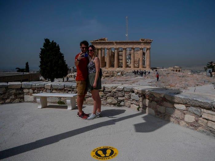 Một cặp đôi khách du lịch chụp ảnh tại thành cổ  the Acropolis (Athens)