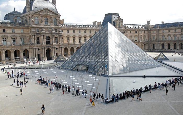 Du khách xếp hàng để vào Kim tự tháp ở bảo tàng Louvre