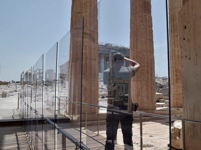 Mặc dù địa điểm Acropolis ở ngoài trời và có thể chứa tới 2.000 người cùng một lúc, nhưng chỉ một số lượng khách du lịch hạn chế sẽ được phép và các biện pháp an toàn, bao gồm cả dải phân cách bằng nhựa, sẽ khuyến khích họ tôn trọng các quy tắc xa cách xã hội.Khách du lịch chụp ảnh phía sau tấm mica ở lối vào Acropolis