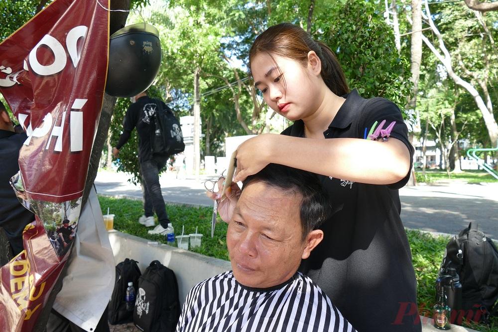 Trương Ngọc Đan Thanh, một trong những người thợ nữ duy nhất trong nhóm bạn trẻ đang tỉ mỉ tạo kiểu tóc cho khách. Đan Thanh cho biết, khoảng thời gian đi cắt tóc ngoài vỉa hè đã giúp cô rèn dũa nghề và lan tỏa lòng nhân ái đến những hoàn cảnh khó khăn. Cô gái sinh năm 1993 dự định sẽ ra nước ngoài để phát triển niềm đam mê của mình trong thời gian tới.