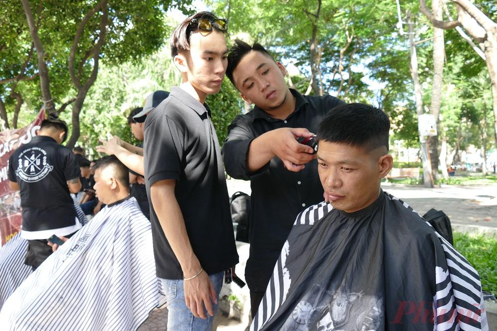 """Vừa quan sát, anh Nguyễn Hữu Hòa, trưởng nhóm, nhắc nhở mọi người về việc chuẩn bị ghế để phục vụ khách đến cắt tóc. """"Trung bình một ngày, chúng tôi cắt miễn phí cho khoảng 20 người, đủ các đối tượng, từ xe ôm công nghệ đến người bán vé số, học sinh, người nước ngoài, hễ ai có nhu cầu thì chúng tôi đều phục vụ tận tình"""", anh Hòa nói."""