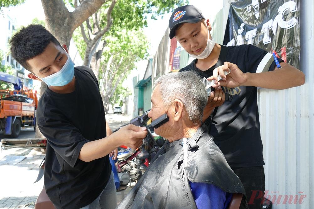 """Với mô hình trên, tấm bảng """"Cắt tóc từ thiện"""" cũng mọc lên tại một góc nhỏ trên tuyến đường Lữ Gia (Quận 11). Dưới cái nắng oi ả, một nhóm bạn trẻ đang cố chào mời khách đi đường vào cắt tóc miễn phí. Những bạn trẻ này cắt tóc từ 10-15 giờ vào các ngày 3, 5, 7 trong tuần."""