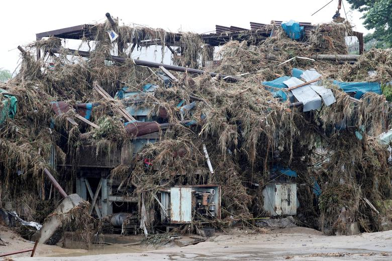 Nhật Bản đang phải hứng chịu những hậu quả nặng nề từ lũ lụt, những cơn mưa giông kéo dài. Trong ảnh, một toà nhà hư hại được bao phủ bởi đất đá, cây cối bị