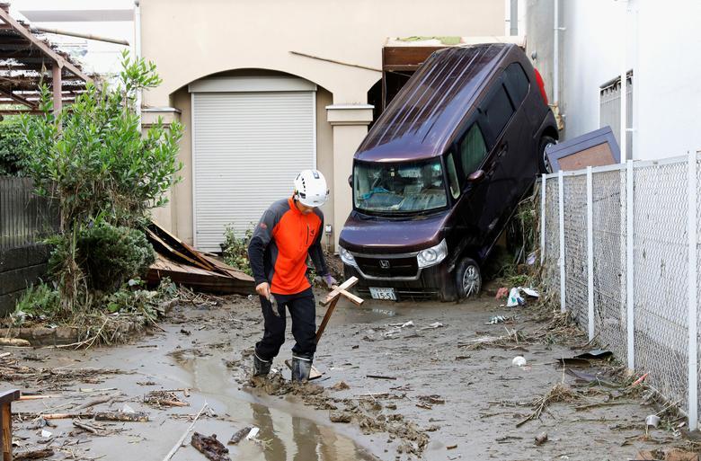Người công nhân đang tiến hành dọn dẹp đống đổ nát xung quanh một căn nhà chịu ảnh hưởng nặng nề bởi mưa bão. Dưới mặt đất, sìn bùn đóng thành lớp dày khiến việc di chuyển rất khó khăn.