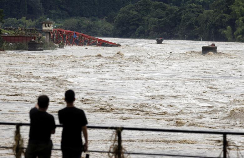 Người dân đứng nhìn cây cầu Kuma ( thị trấn Kuma, Kumamoto) bị cuốn trôi trong dòng nước chảy xiết.