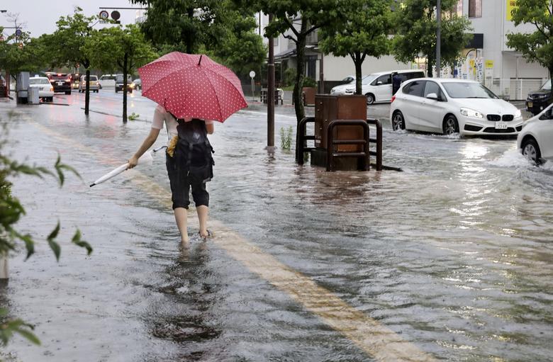 Nhiều nơi, lượng mưa lên đến 18-25cm, gây ngập úng đường sá. Trong ảnh, một người đang phải lội nước bì bõm để đến nhà ga ở tỉnh Saga.