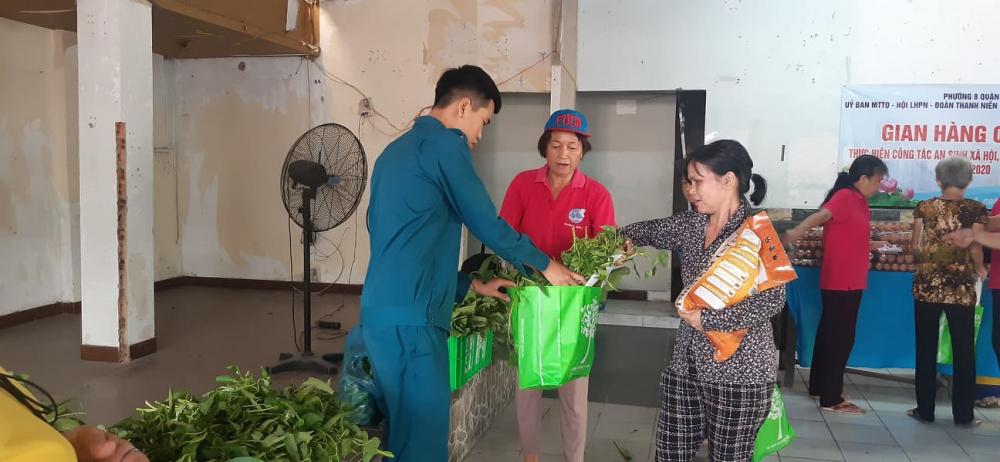 Cán bộ, hội viên cùng dân quân tự vệ của phường cùng giúp người dân đi chợ.