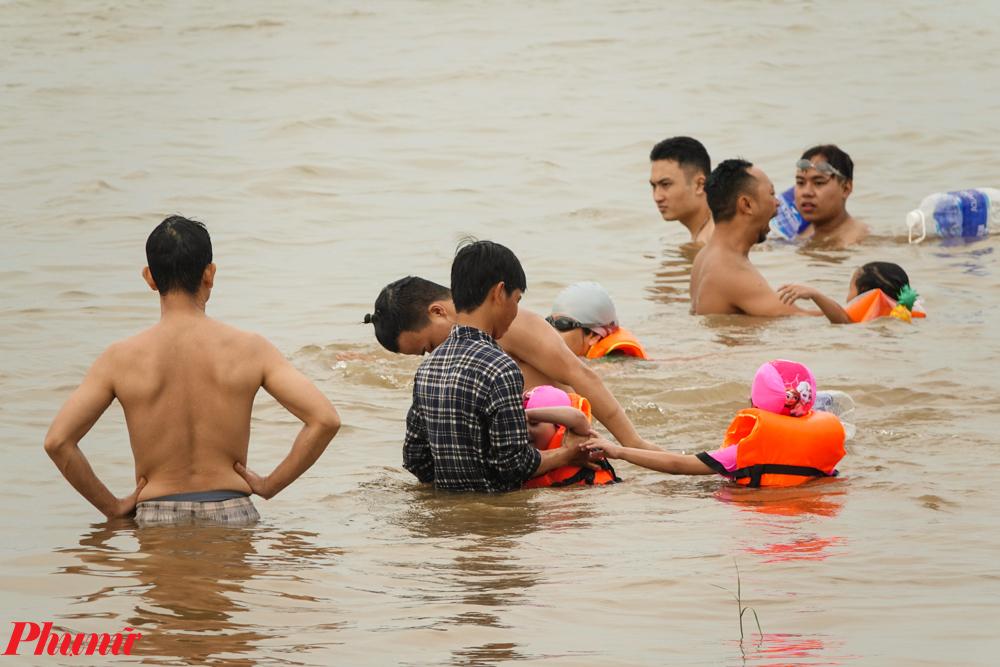 Nhiều em nhỏ cũng được gia đình cho ra đây để tập bơi.