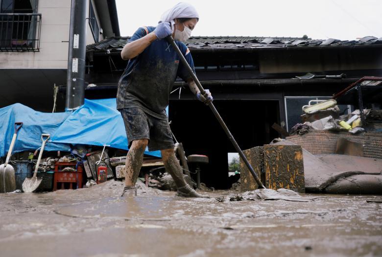 Một người phụ nữ đang dọn dẹp bùn đất trong nhà sau khi cơn lũ cuốn qua.