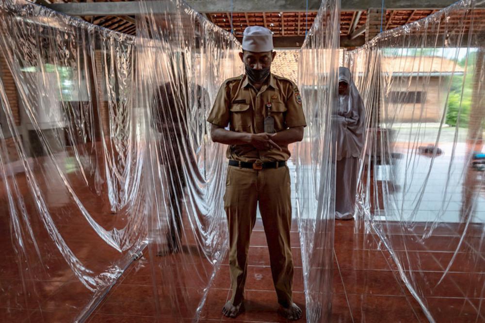 Semarang, tỉnh Trung Java, 18/5/2020: Các tín đồ đạo Hồi cầu nguyện giữa những tấm màn ngăn cách bằng nhựa, để ngừa sự lây lan của virus gâyy ra đại dịch Covid-19 (Antara Foto)