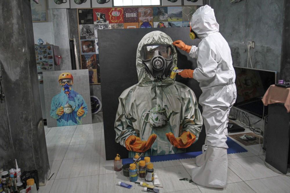 Một hoạ sĩ mặc bộ đồ bảo vệ đang hoàn tất bức tranh vẽ một nhân viên y tế, với thông điệp ca ngợi những người ở tuyến đầu chống đại dịch Covid-19. Hình chụp ở Sleman, tỉnh Yogyakarta, Indonesia, ngày 5/6/2020 (Antara Foto)