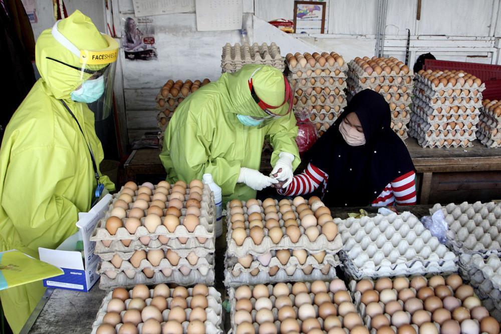 Nhân viên y tế thu thập mẫu máu từ một nhà cung cấp trứng để xét nghiệm virus corona chủng mới, trong quá trình xét nghiệm hàng loạt ở một khu chợ tại Makassar, Nam Sulawesi, ngày 12/5/2020 (AP Photo)