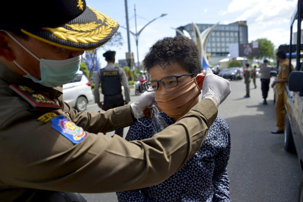 Banda Aceh, ngày 18/5/2020: Viên cảnh sát điều chỉnh khẩu trang của một người lái xe máy, sau khi anh ta bị chặn lại vì không chịu đeo khẩu trang giữa đại dịch Covid-19 (AFP Photo)