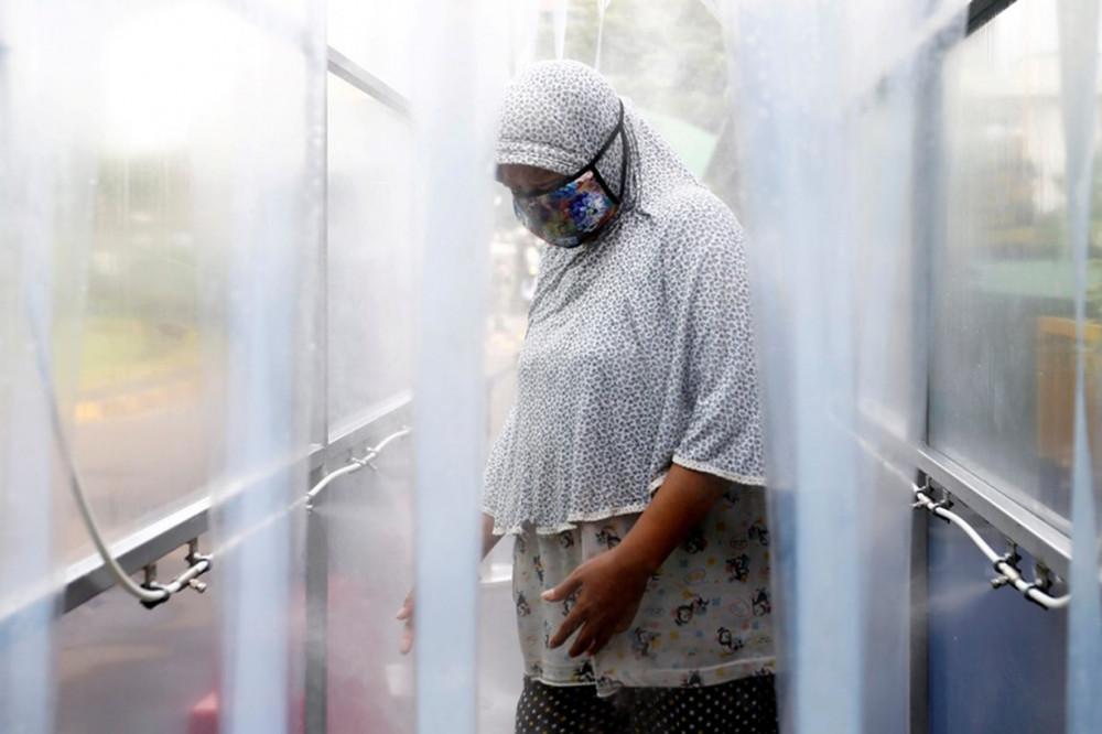 Jakarta, 4/5/2020: Một phụ nữ đeo khẩu trang đứng trong buồng khử trùng, trước khi được nhận gạo từ trạm ATM phân phối tự động (Reuters)