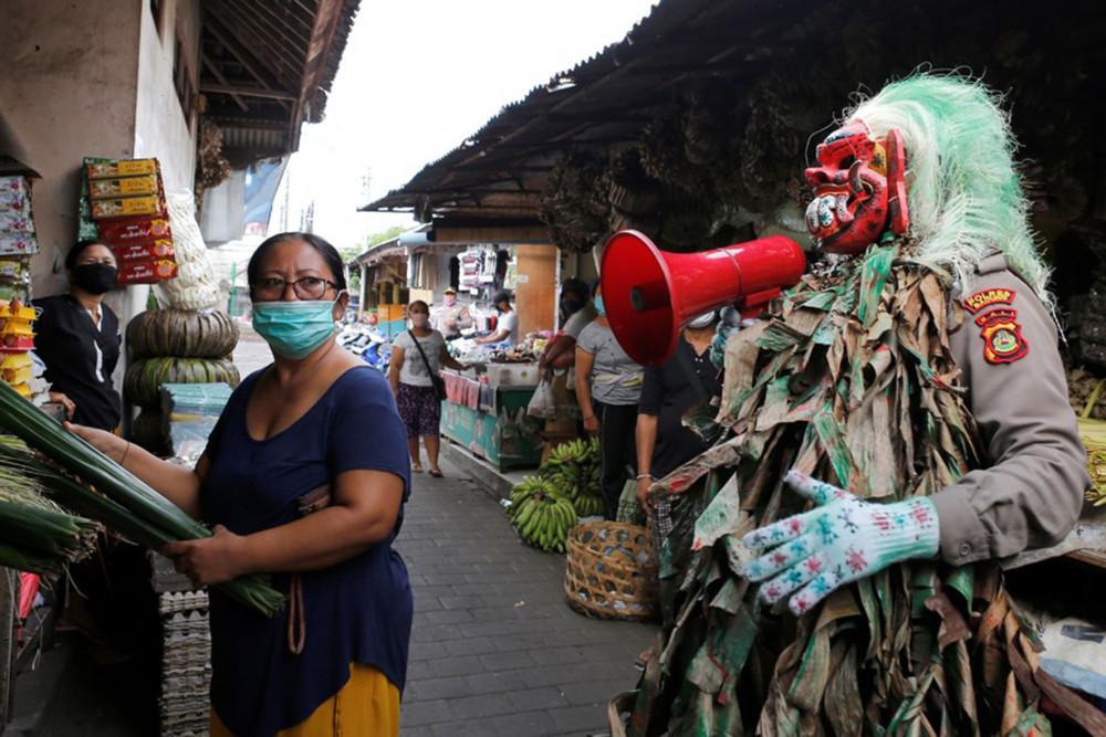 """Một sĩ quan cảnh sát đeo mặt nạ truyền thống celuluk của đảo Bali khi làm nhiệm vụ giám sát việc thực hiện các biện pháp phòng ngừa Covid-19 tại một khu chợ ở Bali, hôm 14/5/2020 (AP Photo). Nhiều nơi ở Indonesia đã khai thác niềm tin rộng rãi vào siêu nhiên, trong văn hóa dân gian, khi thực hiện các biện pháp giãn cách xã hội. Chẳng hạn, ở huyện Sragen, tỉnh Trung Java, những kẻ vi phạm sẽ bị nhốt vào những ngôi nhà bỏ hoang, mà người địa phương tin rằng đó là những """"căn nhà bị ma ám""""."""