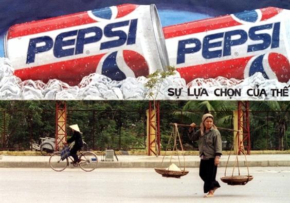 Một người phụ nữ đi qua trước bảng quảng cáo Pepsi ở Hà Nội vào tháng 2/1995, một năm sau khi lệnh cấm vận thương mại được dỡ bỏ. (Ảnh: Reuters)