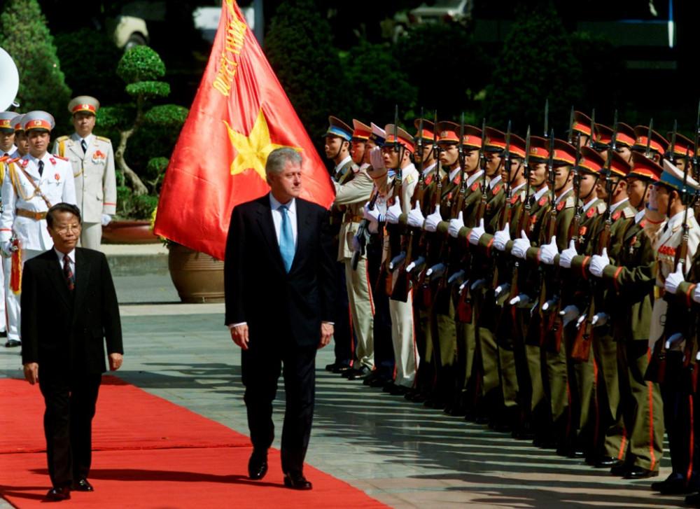 """Vào ngày 16-19/11/2000, sáu năm sau khi dỡ bỏ lệnh cấm vận, Tổng thống Clinton trở thành nguyên thủ quốc gia đầu tiên của Mỹ đến thăm Việt Nam kể từ trước chiến tranh. Trong chuyến thăm, ông nêu rõ: """"Lịch sử mà chúng tôi để lại thực sự đau đớn và khó nguôi ngoai. Chúng ta không được quên nó, nhưng chúng ta cũng không được để nó ảnh hưởng mối quan hệ này"""". (Ảnh: Reuters)"""