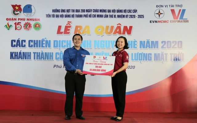 Bà Đặng Mỹ Ly - Bí thư đoàn thanh niên EVNHCMC trao bảng tượng trưng công trình điện mặt trời áp mái cho Nhà thiếu nhi Q. Phú Nhuận.